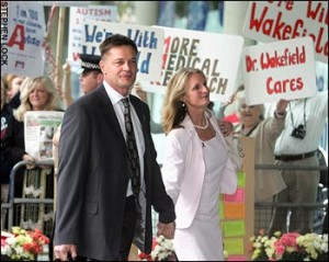 Andrew Wakefield attends the hearing in 2008, flanked by his wife and supporters displaying placards.